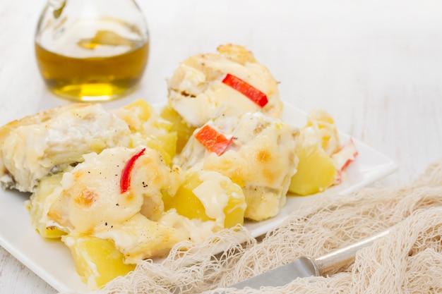 Dorsz z ziemniakami i sosem na białym talerzu