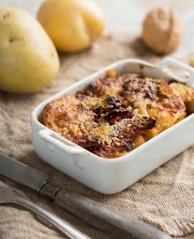 Dorsz z ziemniakami zapiekany w piekarniku w zapiekance. ścieśniać