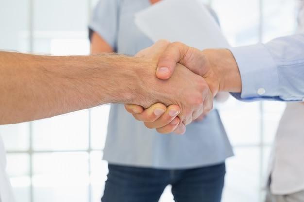 Dorywczo biznesmenów, ściskając ręce