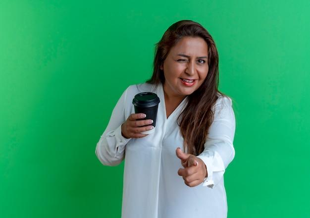 Dorywczo kaukaski kobieta w średnim wieku trzyma filiżankę kawy i pokazuje gest