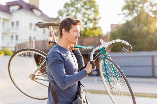 Dorywczo mężczyzna przewożący rower z boku