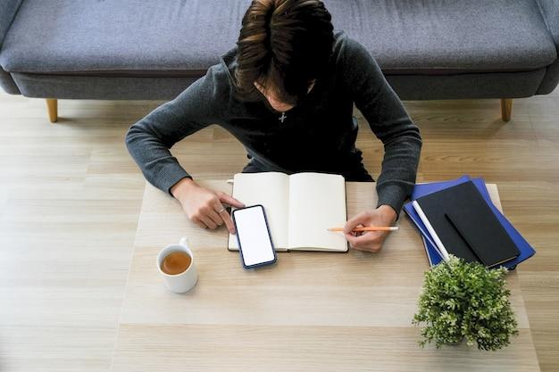 Dorywczo młody człowiek siedzi na drewnianej podłodze w salonie przy użyciu telefonu komórkowego i robiąc notatkę na notesie.