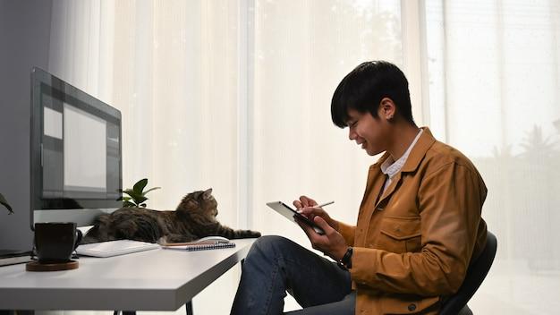 Dorywczo młody projektant graficzny siedzi ze swoim kotem w domowym biurze i pracuje z cyfrowym tabletem.