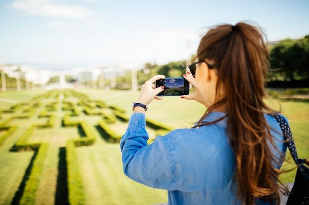 Dorywczo piękna młoda kobieta pozuje do zdjęcia smartfona w parku miejskim w lecie.
