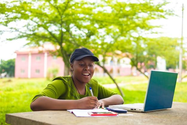 Dość afrykańska studentka jest podekscytowana, gdy pracuje nad swoim zadaniem w kampusie