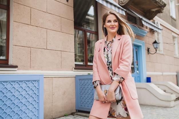 Dość atrakcyjna stylowa uśmiechnięta kobieta spaceru ulicą miasta w różowym płaszczu wiosenny trend w modzie trzymając torebkę, słuchając muzyki na słuchawkach
