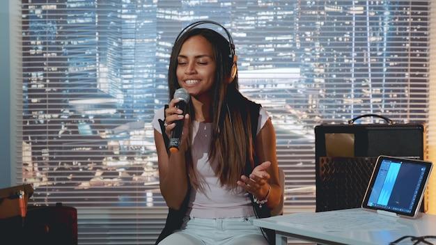 Dość czarna dziewczyna w słuchawkach śpiewa do mikrofonu i nagrywa piosenkę w domowym studio