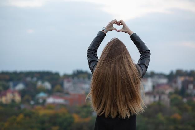 Dość długowłosy model przedstawiający symbol serca dwiema rękami na tle miasta. miejsce na tekst