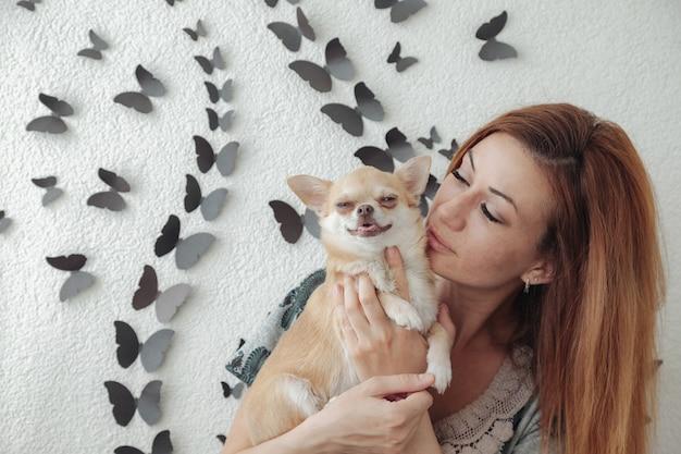 Dość dojrzała kobieta z psem chihuahua w rękach na balkonie w domu. kobieta w średnim wieku i jej piesek chihuahua. koncepcja miłości do zwierzaka i przyjaciela rodziny