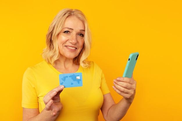 Dość dorosła pani w jasnych ubraniach, oglądając aparat i pozując z niebieskim telefonem i kartą kredytową.