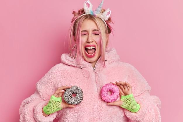 Dość emocjonalna kobieta wykrzykuje głośno, jest bardzo szczęśliwa, trzyma dwa glazurowane pączki, trzyma szeroko otwarte usta, nosi opaskę na głowę jednorożca i futro