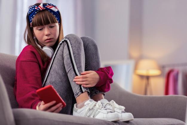 Dość. emocjonalny dzieciak obejmujący jej nogi, wpatrując się w swój gadżet