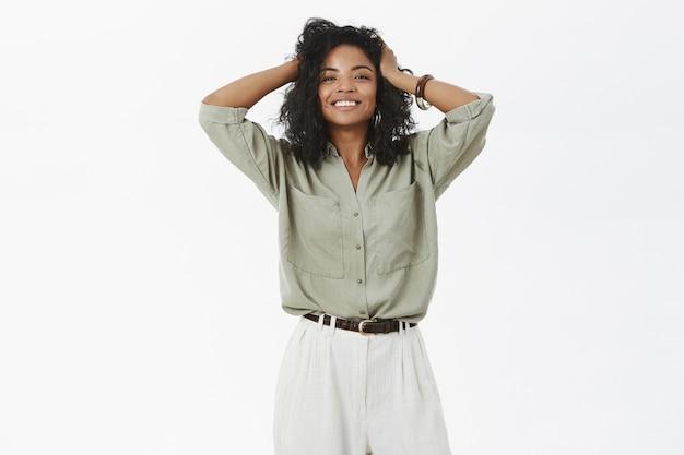 Dość energiczna i kobieca szczęśliwa afroameryka zadowolona z nowej fryzury