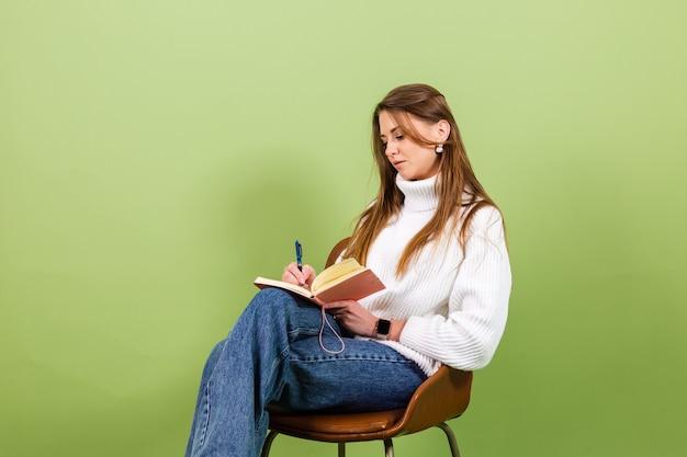 Dość europejska kobieta w dorywczo biały sweter na białym tle, ładny szczęśliwy siedzieć na krześle z notatnikiem i piórem