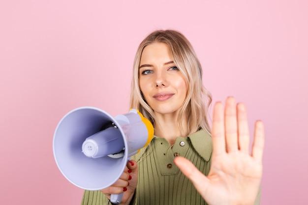 Dość europejska kobieta w swobodnym swetrze na różowej ścianie. niezadowolony poważny z megafonem robi znak stopu z dłonią