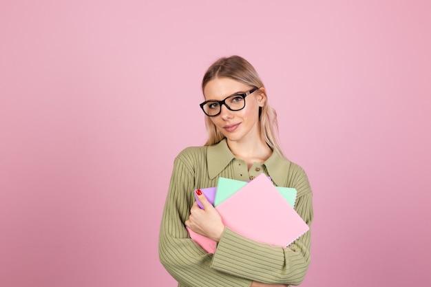 Dość europejska kobieta w swobodnym swetrze na różowej ścianie