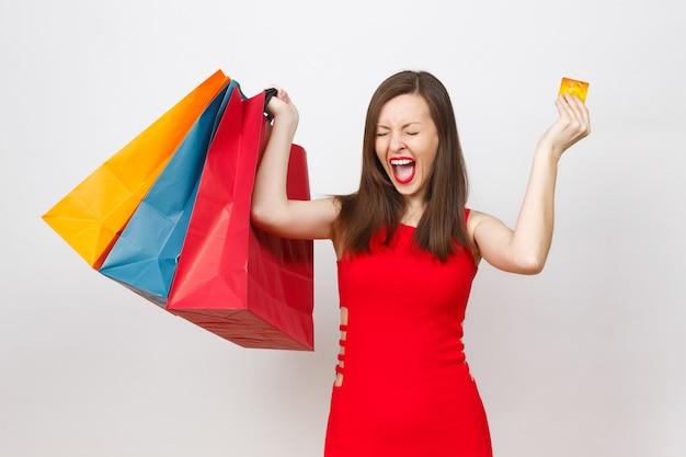 Dość imponujące modne młode brązowe włosy kobieta w czerwonej sukience trzyma kartę kredytową, wielokolorowe pakiety z zakupami po zakupach na białym tle. skopiuj miejsce na reklamę.