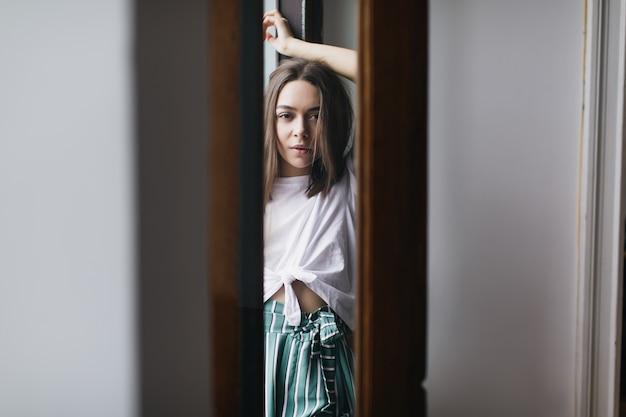 Dość kaukaska kobieta o spokojnym wyrazie twarzy, która chłodzi się w swoim mieszkaniu. wspaniała brunetka dziewczyna w ubranie pozuje w domu.
