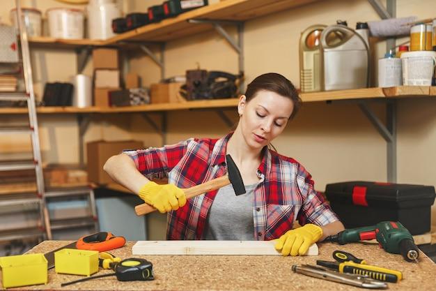 Dość kaukaska młoda kobieta o brązowych włosach w koszuli w kratę, szarej koszulce, żółtych rękawiczkach pracujących w warsztacie stolarskim na drewnianym stole z różnymi narzędziami, wbijanie gwoździ w deskę młotkiem.