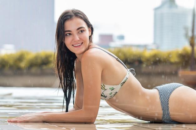 Dość kaukaski kobieta model nosić bikini w deszczu.