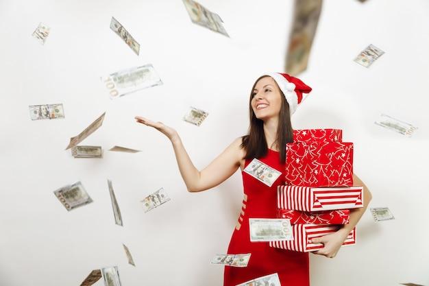 Dość kaukaski młoda kobieta szczęśliwa w czerwonej sukience i boże narodzenie kapelusz, trzymając pudełka i banknoty pieniądze na białym tle. santa dziewczyna z teraźniejszością i gotówką odizolowywającą. koncepcja wakacje nowy rok 2018.