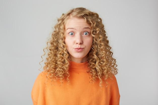 Dość kręcona blondynka patrzy z przodu z wyłupiastymi oczami na białej ścianie