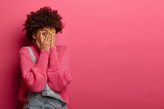 Dość kręcona kobieta zakrywa twarz dłońmi, zagląda przez palce