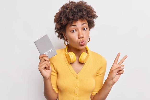 Dość kręcone włosy młoda afro amerykanka trzyma zaokrąglone usta, pokazuje gest pokoju, trzyma paszport, przygotowuje dokumenty do podróży, nosi słuchawki na szyi pozuje na białej ścianie