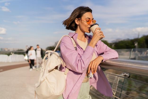 Dość krótkie włosy kobieta w stylowe okulary przeciwsłoneczne, ciesząc się kawą spacerując na świeżym powietrzu w słoneczny dzień