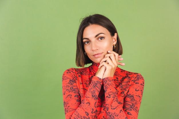 Dość krótkie włosy kobieta z lekkim makijażem złote kolczyki czerwona chińska bluzka z nadrukiem smoka na zielono, pozytywne emocje, pewny siebie uśmiech