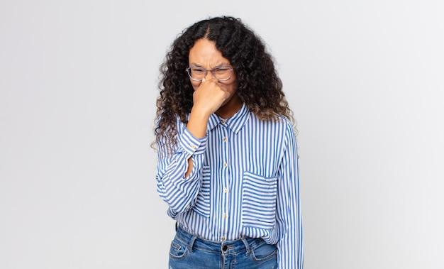 Dość latynoska kobieta czuje się zniesmaczona, trzyma nos, aby nie czuć cuchnącego i nieprzyjemnego smrodu