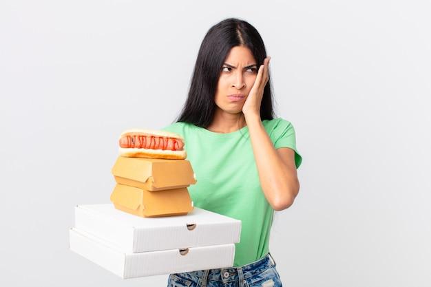 Dość latynoska kobieta czuje się znudzona, sfrustrowana i senna po męczących i trzymających na wynos pudełkach z fast foodami