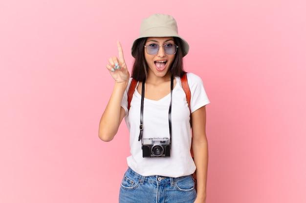Dość latynoski turysta czuje się jak szczęśliwy i podekscytowany geniusz po zrealizowaniu pomysłu z aparatem fotograficznym i kapeluszem