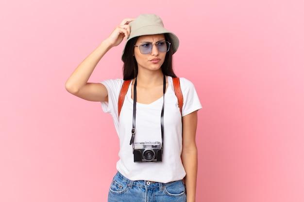 Dość latynoski turysta czuje się zdezorientowany i zdezorientowany, drapiąc się w głowę aparatem fotograficznym i kapeluszem