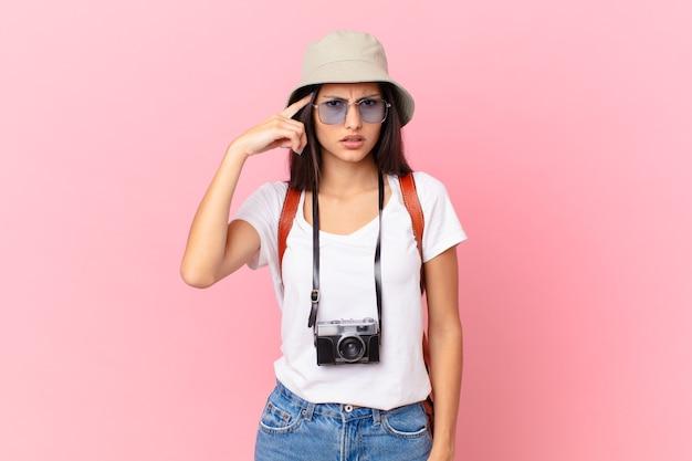 Dość latynoski turysta czuje się zdezorientowany i zdezorientowany, pokazując, że jesteś szalony z aparatem fotograficznym i kapeluszem