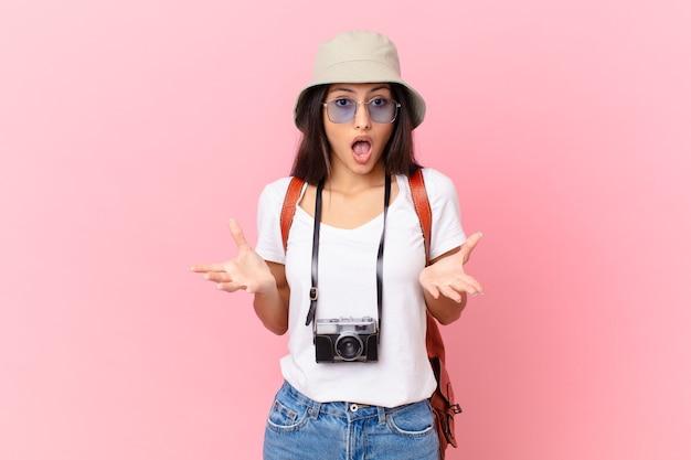 Dość latynoski turysta, który czuje się bardzo zszokowany i zaskoczony aparatem fotograficznym i kapeluszem