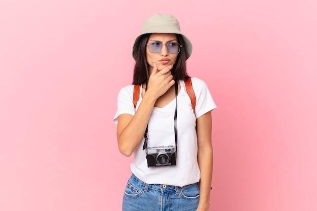Dość latynoski turysta myślący, mający wątpliwości i pomylony z aparatem fotograficznym i kapeluszem