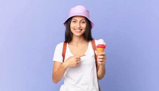 Dość latynoski turysta wyglądający na podekscytowanego i zaskoczonego, wskazujący na bok i trzymający lody