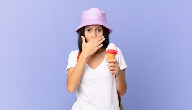 Dość latynoski turysta zakrywający usta dłońmi zszokowany i trzymający lody