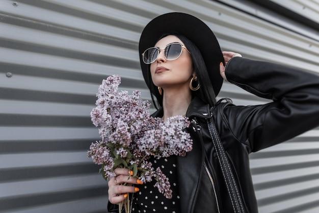 Dość miejska kobieta w modnym kapeluszu w stylowej skórzanej kurtce w okularach przeciwsłonecznych trzyma w ręku bukiet bzu. piękne dziewczyny w czarnych modnych ubraniach pozowanie z pięknymi kwiatami na zewnątrz. wiosna w stylu.