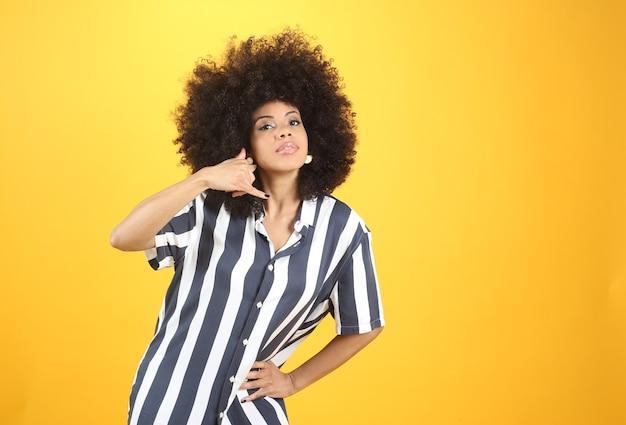 Dość młoda afro kobieta, z gestem połączenia