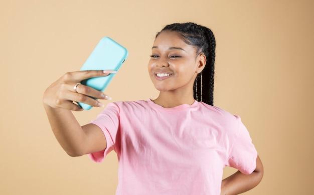 Dość młoda afrykańska kobieta robi selfie ze swoim beżowym tłem smartfona
