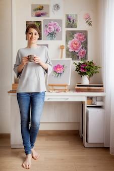 Dość młoda artystka boso w codziennych ubraniach pije kawę, relaksując się po napisaniu szkicu jasnoróżowej róży stojącej na stole na sztalugach i narzędziach