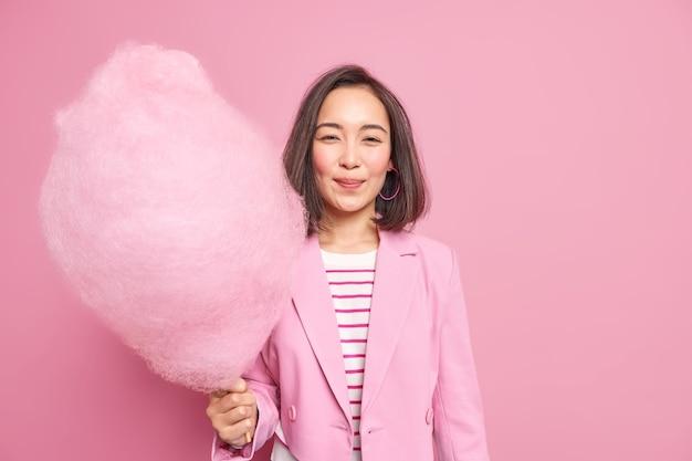 Dość młoda azjatka o ciemnych włosach trzyma smaczną watę cukrową ma słodycze ubrana w stylowe ubrania, będąc w dobrym nastroju na tle różowej ściany, cieszy się wolnym czasem podczas weekendu.