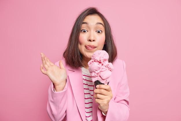 Dość młoda azjatka z krótkimi ciemnymi włosami trzyma duże apetyczne lody oblizuje usta cieszy letni deser podnosi dłoń ubrana w elegancką kurtkę na białym tle nad różową ścianą. pyszne lody
