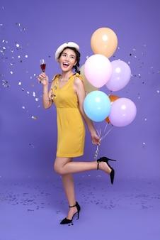 Dość młoda azjatycka kobieta na przyjęciu uroczystości trzymając kolorowy balon i kieliszek do wina z cieszyć się z konfetti spadającymi wszędzie na nią. szczęśliwego nowego roku lub wigilię z okazji urodzin koncepcja