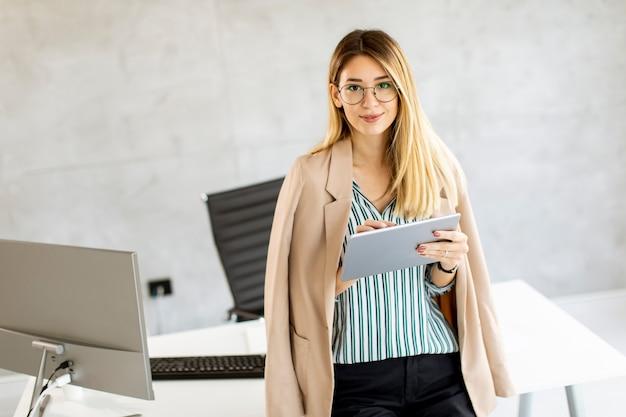 Dość młoda biznesowa kobieta trzymając cyfrowy tablet i stojąc w nowoczesnym biurze