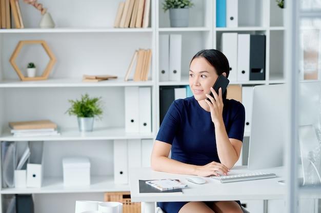 Dość młoda bizneswoman brunetka siedzi przy biurku z smartphone