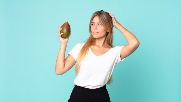 Dość młoda blond kobieta trzyma mango
