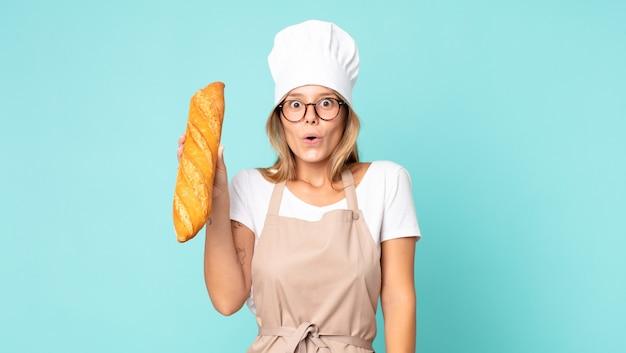 Dość młoda blond kucharz kobieta trzyma bagietkę z chlebem
